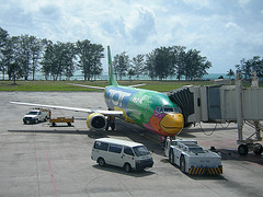 Phuket travel guide with nok air air craft parks on the run way.