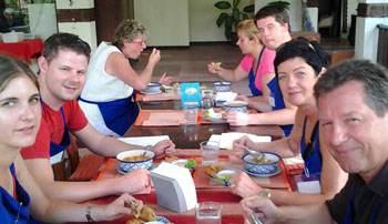 Guest learning Phuket Cookery School Thai Cooking Class with smileing faces.