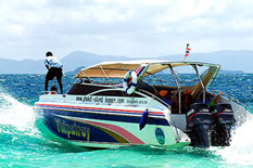 Phi Phi Island private speedboat rent with man standing on the boat.